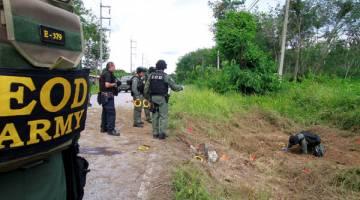 HATI-HATI: Pegawai memeriksa kawasan di mana sebutir bom meletup di wilayah Yala di selatan Thailand semalam. — Gambar Reuters