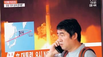 PROVOKASI TERBAHARU: Seorang lelaki melintasi skrin televisyen yang melaporkan mengenai pelancaran misil balistik Korea Utara melalui Jepun ke Pasifik, di Seoul semalam. — Gambar Reuters