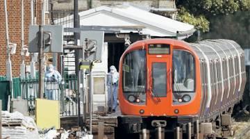 MENGGEMPARKAN: Pegawai forensik polis menjalankan siasatan di sekitar kereta api bawah tanah Tube di pelantar stesen Parsons Green London Underground di barat London, kelmarin susulan insiden dalam salah satu gerabak di mana satu bekas putih (gambar kanan) terbakar sejurus meletup. — Gambar AFP