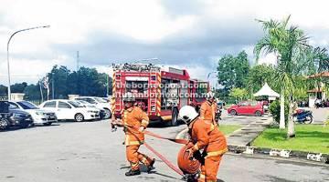 BERSIAP: Anggota bomba membentangkan aliran hos bagi memadamkan kebakaran.