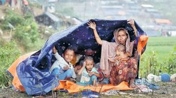 BASAH LENCUN: Sebuah keluarga Rohingya berlindung daripada hujan di bawah kanvas di tepi jalan dekat kem di Cox's Bazar, semalam. — Gambar Reuters