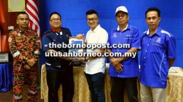DILANCAR: Chan (tiga kanan) menerima cenderahati daripada Jambri selepas merasmikan Skuad Uniti Daerah Sandakan.