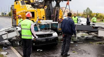 TRAGIK: Para pekerja kecemasan menggunakan kren untuk mengangkat papan tanda jalan yang tumbang menimpa sebuah kereta susulan ribut yang membadai barat Romania di Timisoara, kelmarin. — Gambar Reuters