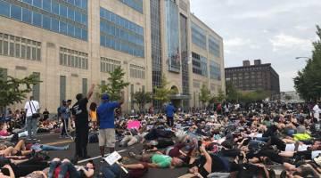 MASIH TEGANG: Para penunjuk perasaan berpura-pura mati pada hari ketiga demonstrasi mengecam keputusan mahkamah dalam kes tembak Smith oleh bekas pegawai polis Stockley di luar ibu pejabat polis di St. Louis, Missouri kelmarin. — Gambar Reuters