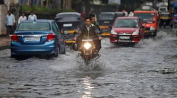 BANJIR KILAT: Orang ramai meredah jalan yang ditenggelami air setelah hujan lebat di Mumbai, semalam. — Gambar Reuters