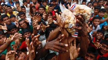 KELAPARAN: Pelarian Rohingya yang kelaparan berebut makanan diagihkan oleh agensi bantuan kemanusiaan di kem pelarian di Cox's Bazar, Bangladesh, kelmarin. — Gambar Reuters