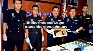 RAMPASAN:  Supt Zulkipli (tengah) bersama pegawai-pegawai JSJ dan Narkotik menunjukkan pistol tiruan, pisau serta dadah yang  dirampas daripada seorang lelaki tempatan di Bintulu.