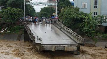 RUNTUH: Penduduk dilihat berkumpul di hujung jambatan yang runtuh akibat banjir di Yen Bai, Vietnam kelmarin. — Gambar AFP