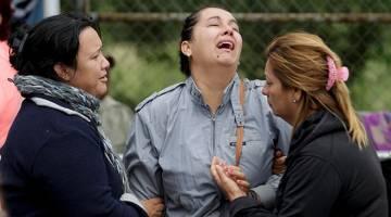 CEMAS: Saudara mara banduan menangis sementara helikopter mencurah air untuk memadam kebakaran selepas rusuhan meletus di penjara Cadereyta, Mexico, pada Selasa lepas. — Gambar Reuters