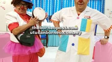 BERKHIDMAT KEPADA MASYARAKAT: Normah (kiri) dan rakannya menjadi badut hospital untuk menghiburkan kanak-kanak yang sakit tenat di hospital. — Gambar oleh Normah Nordin