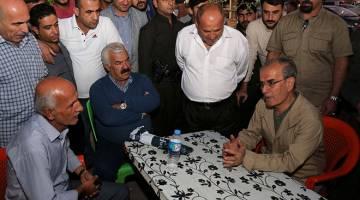 JANGAN MENGALAH: Karim (kanan) bercakap kepada penduduk ketika melawat kawasan kejiranan Shorja di utara Kirkuk, kelmarin. — Gambar AFP