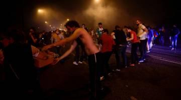 BEKERJASAMA: Orang ramai berbaris di sepanjang lebuh raya membawa baldi berisi air untuk membantu anggota bomba memadam kebakaran hutan di Vigo, barat laut Sepanyol kelmarin. — Gambar AFP