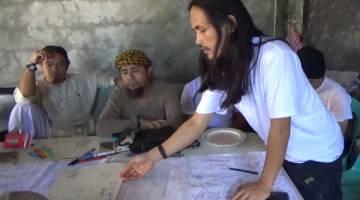 TUMPAS: Gambar fail tidak bertarikh daripada video serahan tentera Filipina pada 18 Jun lalu menunjukkan Hapilon (tengah) dan Abdullah Maute (kanan), adik lelaki Maute yang juga pengasas bersama kumpulan Maute, ketika mereka merancang serangan di satu lokasi tidak didedahkan di pulau Mindanao. — Gambar AFP