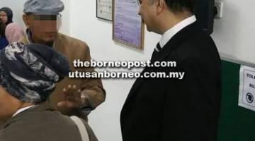 BINCANG: Ahli perniagaan terbabit (kiri) bercakap sesuatu kepada peguam belanya, semalam.
