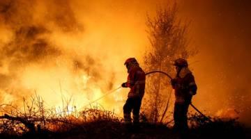 MARAK: Anggota bomba bergegas memadam kebakaran hutan di Cabanoes dekat Lousa, Portugal pada 16 Oktober. — Gambar Reuters