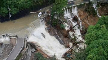 TERJEJAS TERUK: Sebatang jalan runtuh susulan hujan lebat ketika Lan membadai Kishiwada dalam gambar rakaman Kyodo semalam. — Gambar Reuters