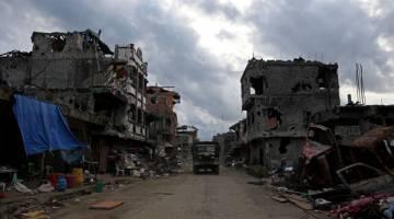 MIRIP SYRIA: Trak tentera melintasi bangunan yang musnah akibat perang di bandar Bangolo, Marawi City kelmarin. — Gambar Reuters