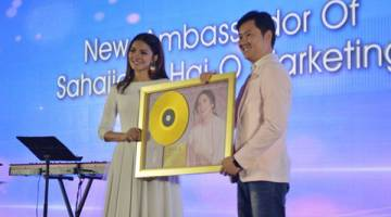 PENGIIKTIRAFAN EMAS: Fazura (kiri) menerima anugerah emas daripada Pengarah Urusan Universal Music Malaysia & Singapura, Kenny Ong baru-baru ini.