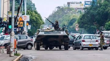 DIGULINGKAN?: Kereta perisai berkawal di persimpangan jalan di Harare kelmarin ketika Mugabe (sisipan) mendakwa beliau                    di bawah tahanan rumah meskipun golongan jeneral menafikan mereka melancarkan kudeta. — Gambar AFP/Reuters