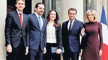 TERPALIT KRISIS: Macron (dua kanan) dan isterinya Brigitte menerima lawatan daripada Hariri, isterinya Lara dan anak lelaki mereka Houssam (kiri) di Istana Elysee di Paris, kelmarin. — Gambar Reuters