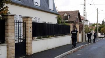 TRAGIK: Pegawai polis berkawal di luar rumah keluarga bekas teman wanita suspek di Sarcelles, kelmarin. — Gambar AFP