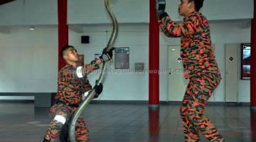 KEMAHIRAN: Muhammad Azizi (kiri) dan Safiq menunjukkan kemahiran mengendalikan haiwan berbisa ular tedung selar di Akademi Bomba Dan Penyelamat Malaysia Wilayah Timur Wakaf Tapai, Marang. — Gambar Bernama