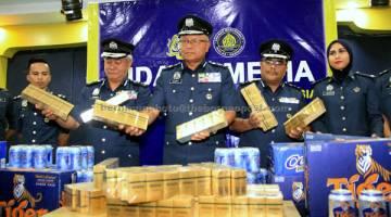 TUMPAS: Zulkifli (tengah) menunjukkan rokok yang dirampas ketika mengadakan sidang media mengenai kes tangkapan dan rampasan minuman keras dan rokok di Kota Kinabalu, semalam. — Gambar Bernama