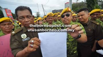 TIDAK WAJAR: Bakry (dua kiri) dan Jafrin menunjukkan laporan polis yang dibuat di IPD Kota Kinabalu pada Rabu.
