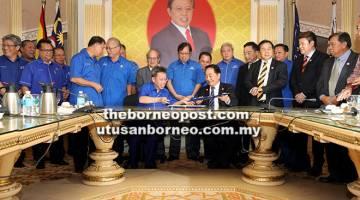 TERMETERAI: Abang Johari (tengah) menyaksikan Dr Sim (duduk kiri) dan Wong menandatangani MoU semalam.
