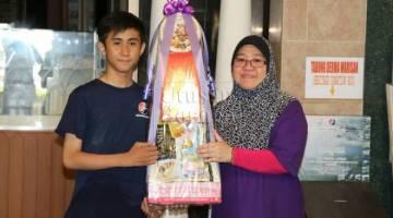 Norraha menyampaikan hamper kepada wakil SMK Petra Jaya.