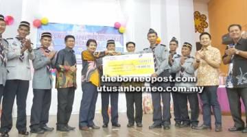 KURUP (lima kiri) menyampaikan replika cek berjumlah RM5,000 kepada PPMCS Daerah Keningau.