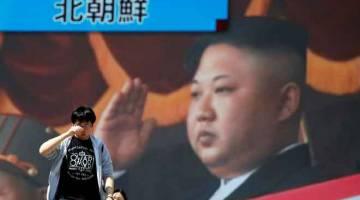 BERITA BAIK: Orang berjalan melintasi monitor di tepi jalan menunjukkan pemimpin Korea Utara dalam laporan berita mengenai pengumuman negara itu untuk menghentikan ujian nuklear dan pelancaran misil, di Tokyo, Jepun semalam. — Gambar Reuters