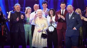 ULANG TAHUN KE-92: Diiringi Charles (kanan), Elizabeth II melambai kepada hadirin semasa menghadiri konsert khas 'Parti Hari Jadi Ratu' di Royal Albert Hall, London kelmarin. — Gambar Reuters