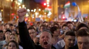 SATU CABARAN: Seorang penunjuk perasaan melaungkan slogan anti-Orban ketika menyertai demonstrasi di Budapest, kelmarin. — Gambar Reuters