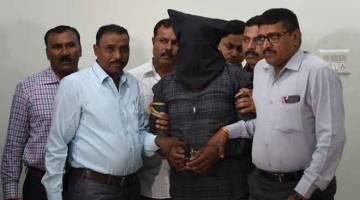 DISIASAT: Pegawai polis India mengiringi Harsayai Gurjar (tengah), salah seorang suspek kes di Surat, susulan penahanannya di Ahmedabad, kelmarin. — Gambar AFP