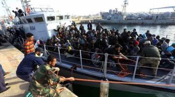 SELAMAT: Pendatang haram dari pelbagai negara Afrika tiba di pangkalan tentera laut di Tripoli kelmarin selepas mereka diselamatkan dari bot getah di luar pantai Zliten. — Gambar AFP