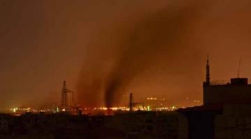 DIBEDIL: Gumpalan asap dilihat di daerah selatan ibu negara Syria, Damsyik, semasa tentera rejim membedil kumpulan militan IS di kem pelarian Palestin, Yarmuk, dan kawasan sekitarnya, pada lewat 19 April lalu. — Gambar AFP