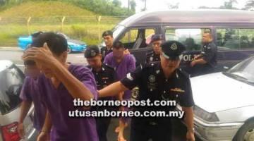DIDAKWA: Lima tertuduh diiringi anggota polis ketika dibawa ke Mahkamah Majistret kelmarin.
