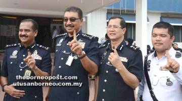 RAMLI (dua kiri) dan Razarudin bersama pegawainya menunjukkan kesan dakwat selepas menunaikan tanggungjawab mengundi awal pada Sabtu.