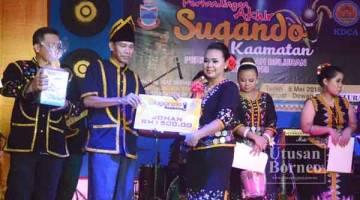 JANAI Sikana menyampaikan hadiah juara Pertandingan Sugandoi Kaamatan     Beluran 2018 kepada Jovinia Umjin bagi mewakili Pegawai Daerah Beluran.