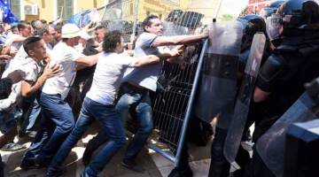 TIDAK PUAS HATI: Penyokong pembangkang bertempur dengan polis perusuh semasa perhimpunan menyeru bagi peletakan jawatan menteri dalam negeri Fatmir Xhafaj apabila adik lelaki beliau terbabit dalam penyeludupan dadah di Tirana kelmarin. — Gambar AFP
