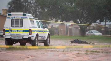 MATI DITEMBAK: Kenderaan polis dilihat berhampiran mayat lelaki yang mati ditembak oleh polis kerana enggan menyerah diri selepas membunuh dua orang di sebuah masjid di Malmesbury, kira-kira 50 kilometer utara Cape Town semalam. — Gambar AFP