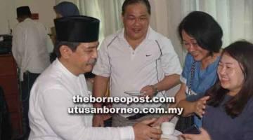 PUPUK PERPADUAN: Krishna (kiri) bersalaman dengan pengunjung pada Majlis Rumah Terbuka Hari Raya Aidilfitri Konsulat Indonesia.