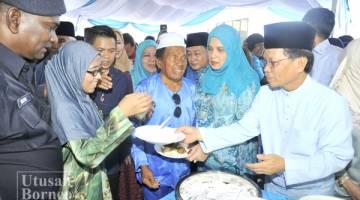 SHAFIE (kanan) dan Shuryani (dua kanan) menghidangkan makanan kepada orang ramai.