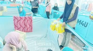 PENOLONG Pegawai Program Domestik IRM Ramlah Halim menyerahkan bantuan kepada mangsa di PPS.