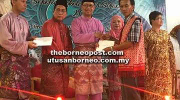 BANTUAN: Julaihi menyampaikan cek geran untuk PIBG Sekolah Zon Sebangan 2018 di Dewan Masyarakat Kampung Sampat Sebangan, Sebuyau.