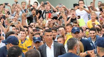PERMULAAN BAHARU: Ronaldo (tengah) tiba untuk menjalani pemeriksaan kesihatan di pusat perubatan Juventus di Stadium Allianz, Turin pada Isnin lepas. — Gambar Reuters