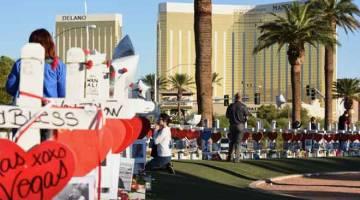 DOA: Gambar fail menunjukkan seorang wanita berdoa, di sebelah 58 salib putih untuk mangsa pembunuhan beramai-ramai pada malam Ahad di Las Vegas Strip, berhampiran Hotel Mandalay Bay pada 6 Oktober, 2017 di Las Vegas, Nevada. — Gambar AFP