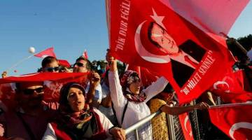 RIUH: Orang ramai menjulang bendera Turki dan potret Erdogan ketika menghadiri upacara untuk menandakan ulang tahun kedua cubaan kudeta di Jambatan Bosphorus di Istanbul, Turki pada 15 Julai lalu. — Gambar Reuters