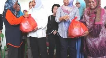 SHURYANI (dua kiri) menyampaikan sumbangan kepada salah seorang mangsa kebakaran.
